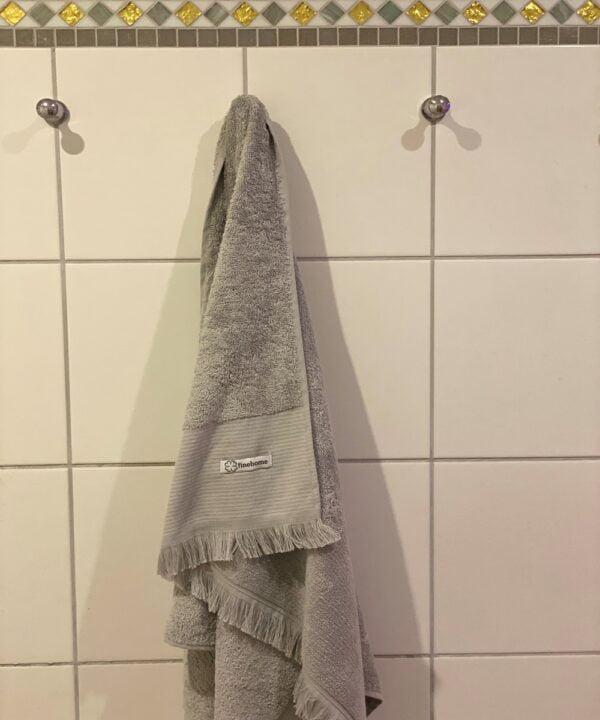 Graat badehaandklaede med frynser i 100% bomuld fra finehome. Maal: 70x140 cm